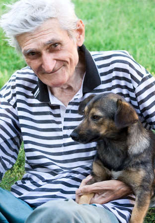 Portrait of happy male senior with his best pal, a cute dog photo