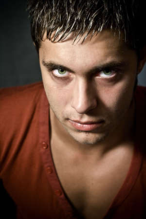 expressive mood: Low key portrait of intense looking guy with green eyes
