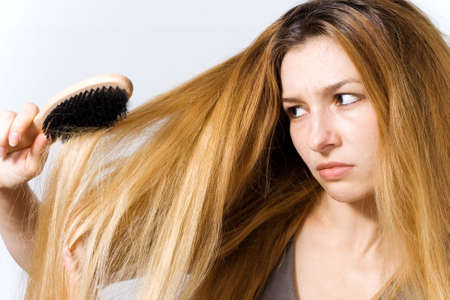grimace: Young woman with hairbrush worried by her tangled hair