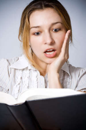 Portrait of young woman amazed by what she is reading photo