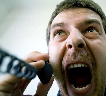 Portrait of angry stressed businessman screaming at the phone photo
