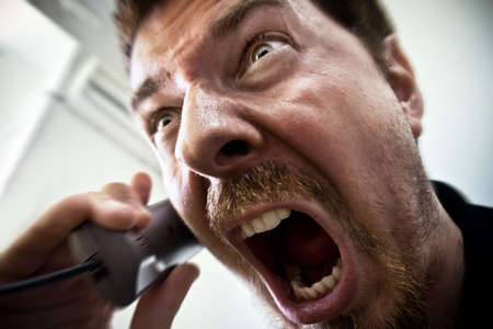 yell: Extreme angry man shouting at the phone