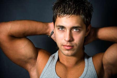 Portrait de jeune homme sexy montrant ses bras musclés