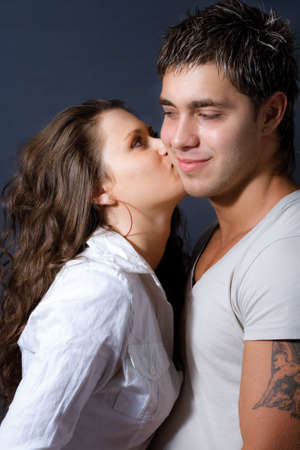 Happy playful couple: young woman kissing her lover photo