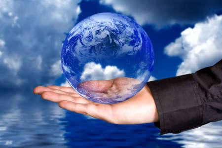 medio ambiente: Proteger el medio ambiente concepto: la mano del hombre la celebraci�n de la Tierra con las nubes y el agua en el fondo