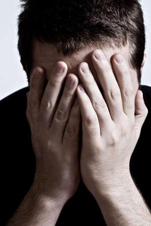 Zenuwinzinking concept: depressieve man die zijn gezicht