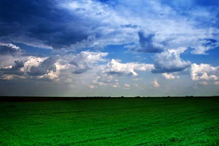 Landscape view of dramatic cloudy sky and green field Stock Photo - 3906223