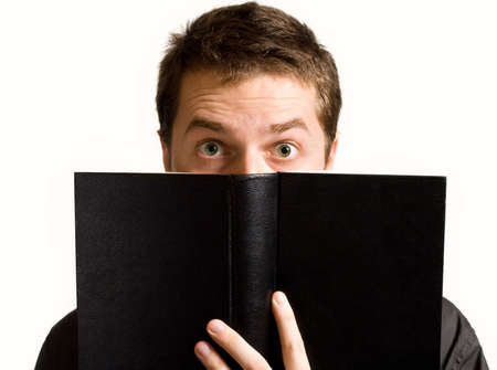 Eyes of surprised man above black book isolated on white photo