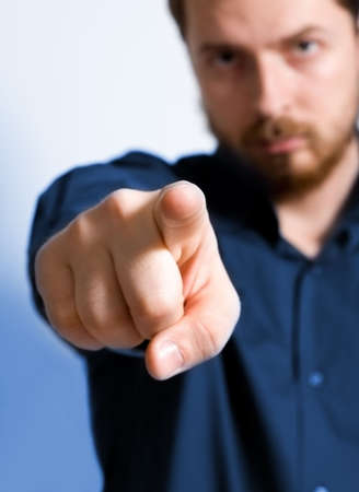 Serious adult man pointing towards viewer - focus on index finger photo