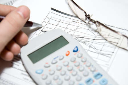 Financial analysis: hand with pen, calculator, glasses and charts photo
