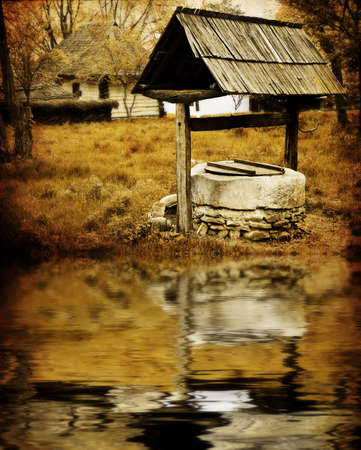Sepia image of ancient water well in rustic village photo