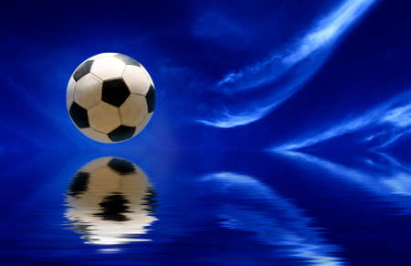 kickball: Soccer ball reflecting in water and blue sky as background Stock Photo