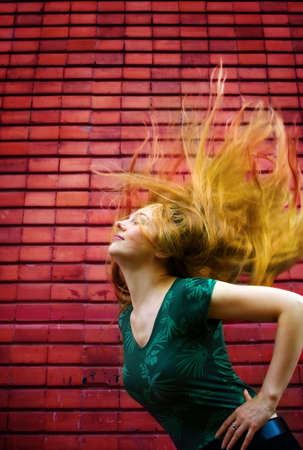 Energic woman with moving hair in front of brickwall Stock Photo - 4164754