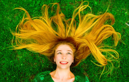 Happy woman with beautiful hair laying in green grass photo