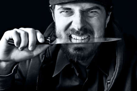 Tough angry guy biting from sharp knife photo