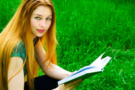 Portrait of young student woman reading outdoors photo
