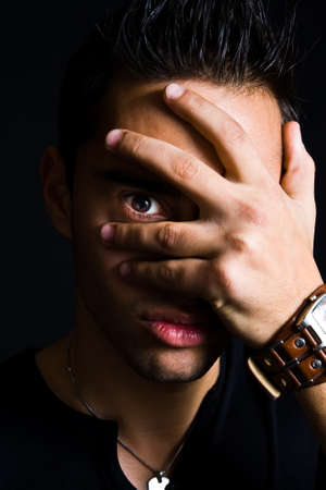 Portrait of shy man hiding with hand on face photo
