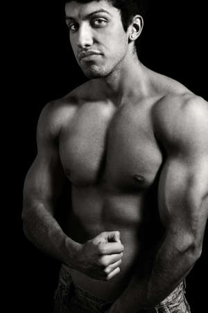 male muscles muscular pecs pectoral sexy young: Tough muscular young man isolated on black background
