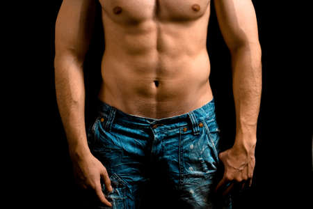 Torso of muscular man with nice abdomen over black photo
