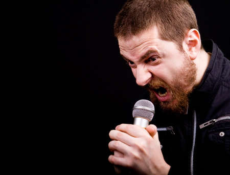 Scream of male angry rocker at the microphone with copyspace photo