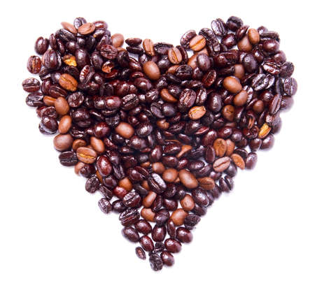 Heart shape formed by bunch of coffee beans isolated on white photo