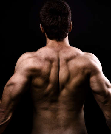 physique: Back muscles of big healthy man over black Stock Photo