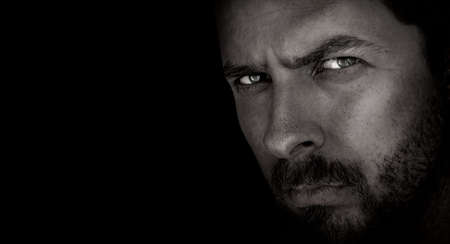 mood moody: Low-key portrait of scary man with evil eyes Stock Photo