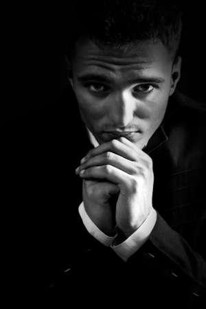 hombre orando: Triste hombre joven en la oscuridad rezar a Dios Foto de archivo