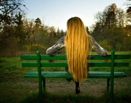 Back of blond woman sitting alone on park bench Stock Photo - 4786311