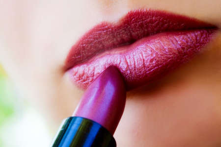 Cosmetics: macro view of female lips and red lipstick photo