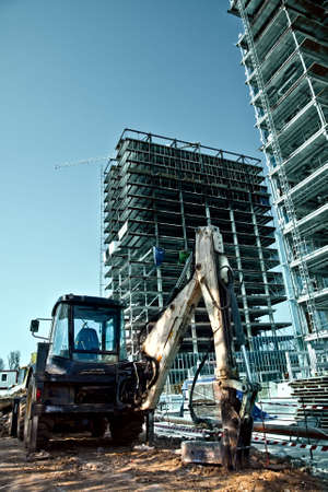 scaffolds: Construction site - excavator and high scaffolds Stock Photo
