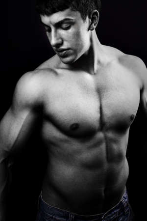 male muscles muscular pecs pectoral sexy young: Portrait of muscular young man in the dark