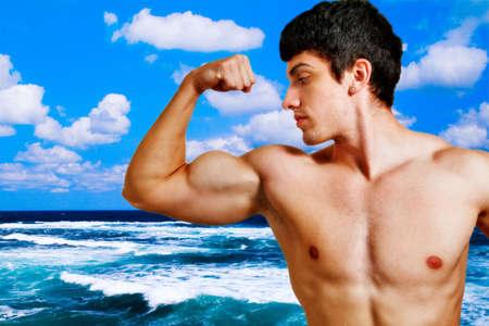 Muscular young man showing his biceps on the beach photo