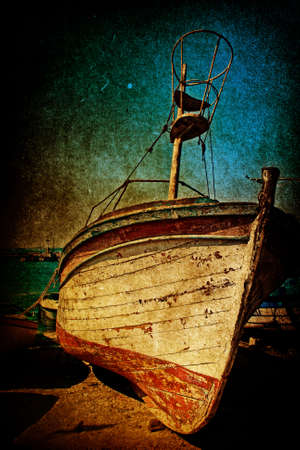 Wreck of one rusty antique boat in grunge style photo