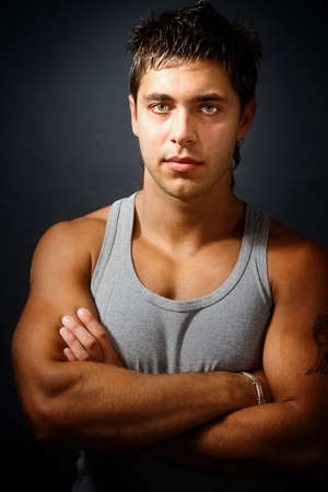 Handsome muscular young man with arms folded photo