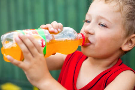 drinking soda: Little boy drinking unhealthy bottled soda