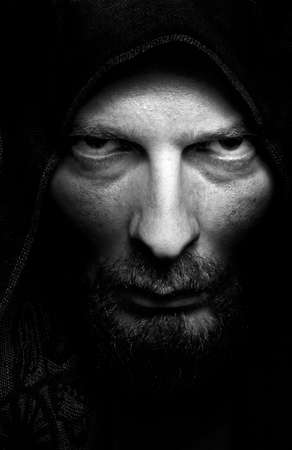 Dark portrait of scary evil sinister bearded man photo