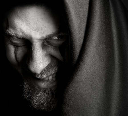 terror: Evil sinister man with malefic grin Stock Photo