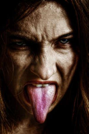 lengua afuera: La mujer Scary mal con la lengua fuera Foto de archivo