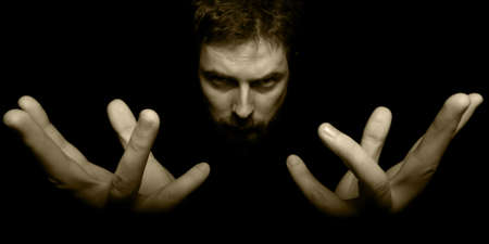 Hands and face of evil magician in darkness Stock Photo - 5636496