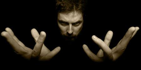 mago: Manos y la cara de malvado mago en la oscuridad Foto de archivo