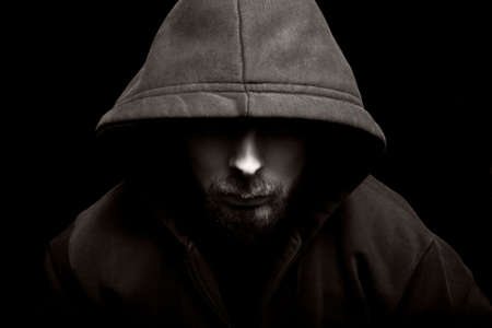 Scary evil man with hood in darkness photo