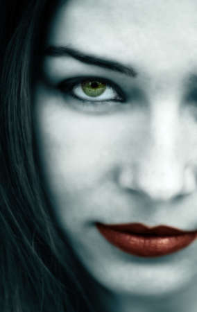 Spooky gothic woman with pale face and red lips photo