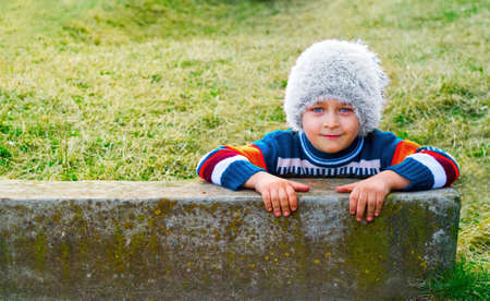 Smiling playful kid with winter white hat on his head photo