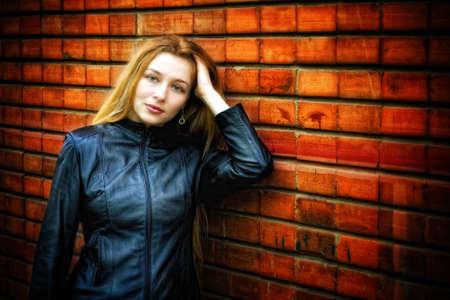 Sexy stylish woman in leather near brick wall Stock Photo - 6181436