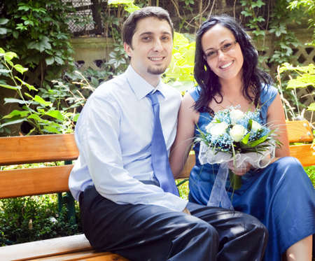 Portrait of happy couple sitting on park bench photo