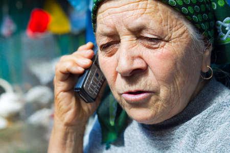 East european senior woman speaking at mobile phone photo