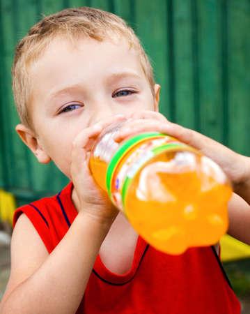 gaseosas: Ni�o sed bebiendo refrescos de naranja embotellada insalubres Foto de archivo