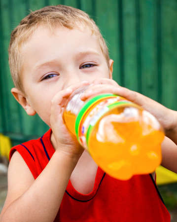 Thirsty child drinking unhealthy bottled orange soda Stock Photo - 6349585