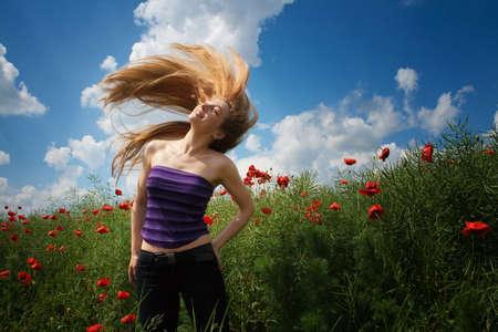 Happy joyful young woman in beautiful poppy field photo